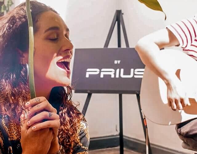 Mujer cantando en un evento de toyota prius con hombre al lado tocando guitarra